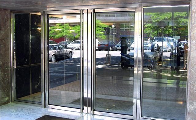 Portal de acceso a edificio de viviendas con dos hojas abatibles realizado en acero inoxidable