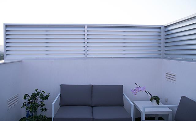Celosía divisoria con lamas curvas de aluminio anodizado en la terraza de una vivienda ático