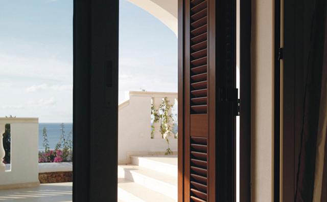 Mallorquina de aluminio en ventanal de acceso a terraza con acabado color madera
