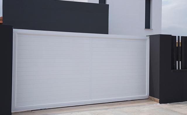 Puerta corredera de aluminio lacado en blanco para acceso a garaje de una vivienda unifamiliar