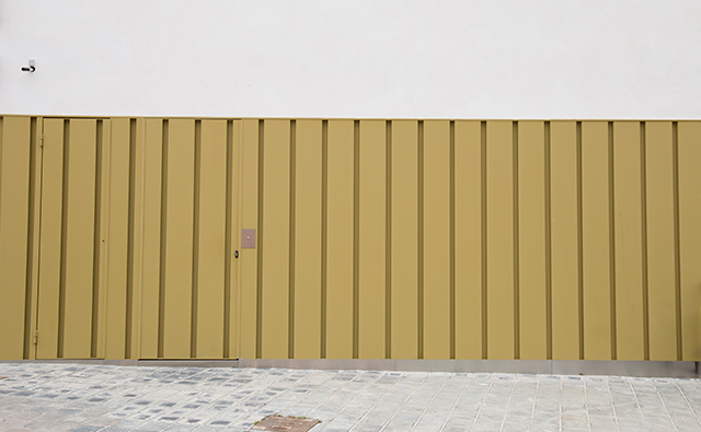 Cancela ciega de hierro lacada en amarillo ocre para acceso a una vivienda unifamiliar
